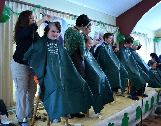 Natalie Caldwell (far left) gets her head shaved by Sherri Reagan, owner of First Impression salon, along with other volunteers at the St. Baldrick's Foundation charity event on March 10 at St. James Episcopal Church in Skaneateles.