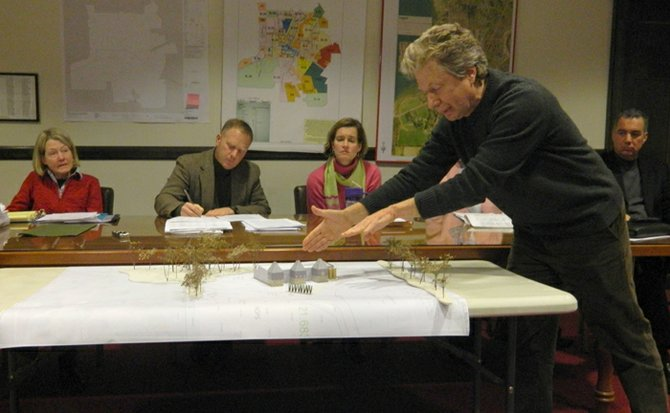 Kurt Ofer, standing, architect for the Empire Brewing Company project, refers to a scale model to explain architectural and design aspects of the proposed brewery on Route 13 to attendees of the village board public hearing on March 4.