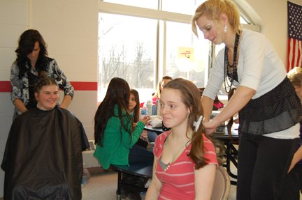 Heather Rivers, a Cosmetology student at CV-Tec, does Chelsea LaGrave's hair while Tracy Donah of Look Good Feel Good beauty salon cuts Barbara Smith's hair during Girls Night out at Beekmantown Central School.