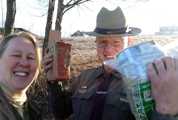 "Patty Wesner and state Trooper Kevin Saunders pose with some of the money that Wesner collected and guarded after it fell out of the back of a Brink's truck onto a rural roadway. Wesner said this week that Saunders told her, ""I can't believe you called us."""