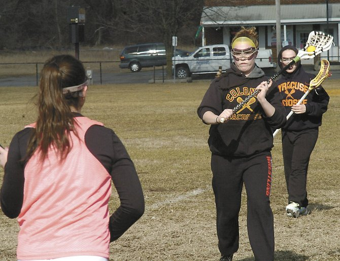 Senior Nicole DiPiazza, second from right, throws a pass to a teammate during last Wednesdays Colonie girls lacrosse practice. The Lady Raiders begin their Suburban Council season March 28 against Guilderland.