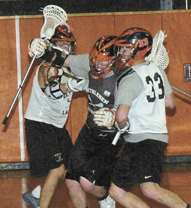 Tyler Bugbee, middle, tries to get around goaltender Dan Comber during last Friday's Bethlehem boys lacrosse team practice. Bugbee and Comber are among the returning players looking to turn the Eagles' fortunes around.