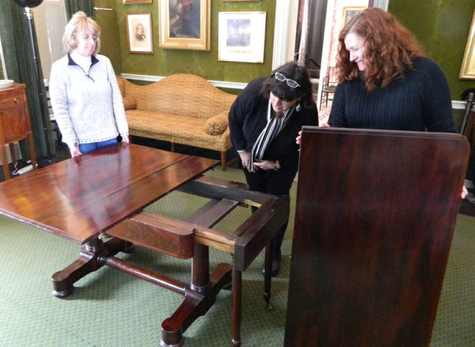 "Lorenzo officials Sharon Cooney, interpretive programs assistant and volunteer docent coordinator, left, Barbara Bartlett, director of Lorenzo, center, and Jacqueline Vivirito, curatorial associate, examine the ""harvest table"" in the mansion's formal dining room and the way it can extend out to accomodate a larger number of people. A recent conservation study revealed that the table had not only drop leaves, but also a swivel top, swivel legs and drop down legs to hold up a table extension."