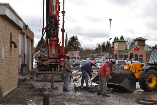 Construction workers remove dirt on Friday, March 29, that was excavated during drilling 850-foot holes pipes sticking out of ground) for the geothermal energy system to be built in the new village hall on Fennell Street.