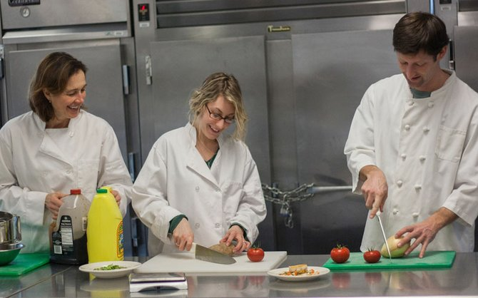 Elizabeth Seeley, Whitney Graham, and Timothy Hayes, prepare food during a Meal Management lab held at the Copper Turret, college-run restaurant.