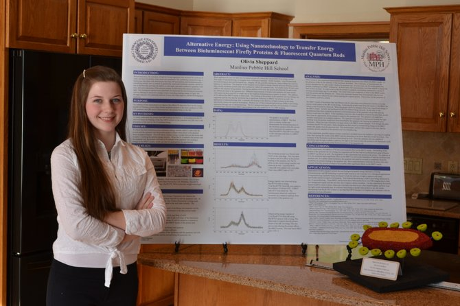Olivia Sheppard with her award-winning presentation demonstrating her research which she conducted at Syracuse University.