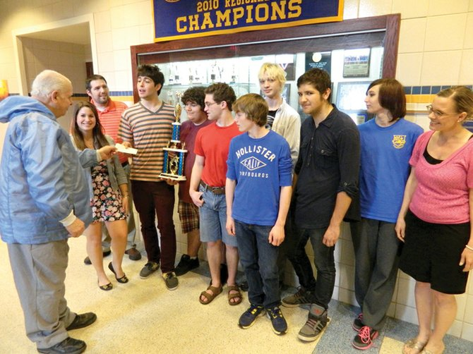 The Cazenovia High School Academic decathlon Team, along with advisors Marty Kelly and Christie Brennock, accept the $1,000 donation from the Cazenovia Lions Club, presented by Allan Youngs, front left.