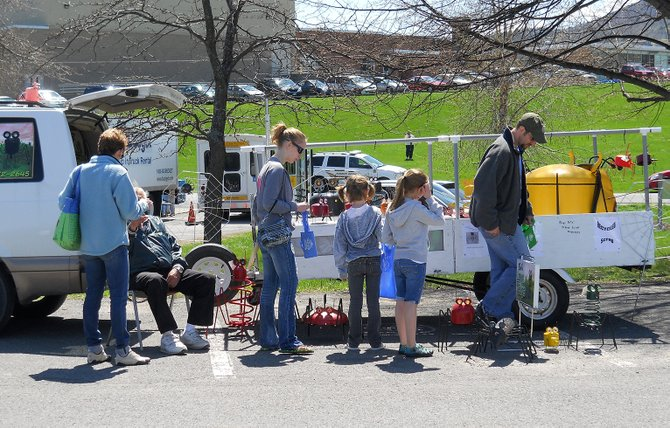 Lawn decorations made from scrap metal will be sold at Go Green Day 2013, which is being held Saturday, April 27, from 8 a.m. to 2 p.m., at Farnsworth Middle School on State Farm Road in Guilderland. Pictured are attends of the first Go Green Day in 2011 viewing decorations.