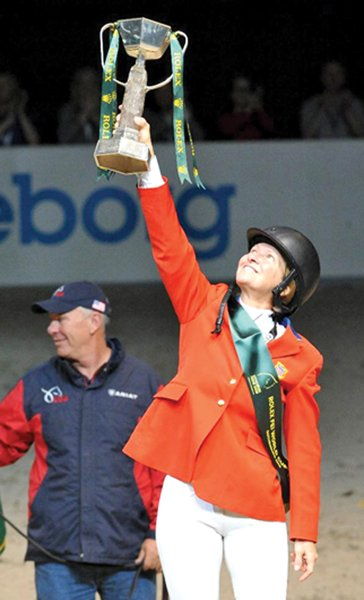 Beezie Madden holds high her world cup after winning last weekend in Sweden.