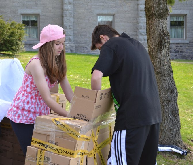 Melissa Biver (left) and Conor Driscoll (right) work on assembling their shelter in the 'shanty town' in Thayer Park built by youth participating in a 30-hour fast for charity last weekend.