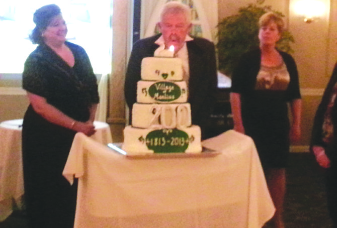 Manlius mayor Paul Whorrall blows out the candle on the village's 200th birthday cake.