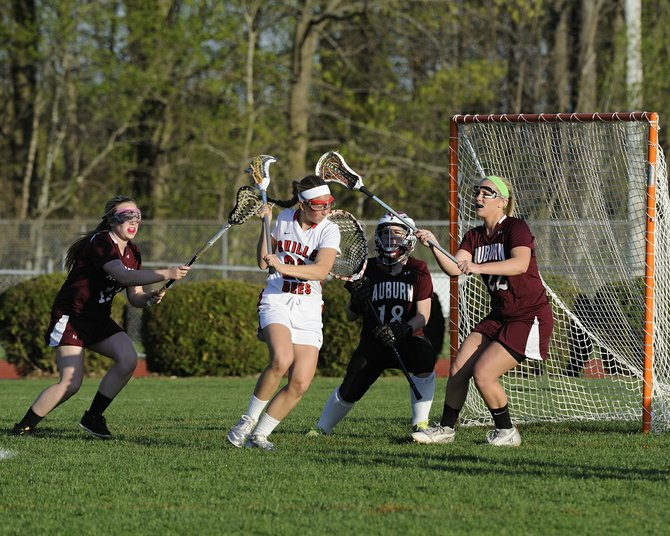Baldwinsville midfielder Taylor Gebhardt (20) has two Auburn defenders, plus goalie Sydney Teeter, in her way as she tries to score in last Thursday's game. Gebhardt had two goals and two assists as the Bees beat the Maroons 15-10.