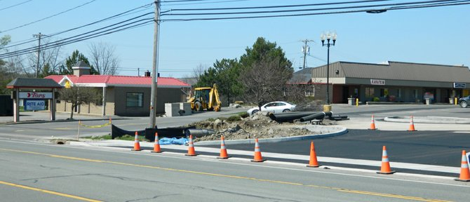 Last week construction crews created a new entrance, front right, to the Tops plaza parking lot off Route 20. The current entrance, near the Tops sign at left, will close this week. The old Kimberly's Ice Cream building, at left, will soon be razed and a new Tops gas station built in its place.