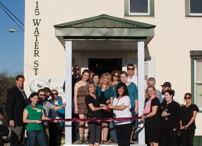 Partners Noelle Ryan Corrado and Amy Mercadante (center) cut the ribbon at their new facility, Asana Wellness Spa, marking their spring grand opening last Friday.