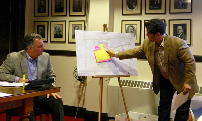 Empire Brewing Company owner David Katleski, right, used a site plan map to show May 6 public hearing attendees a to-scale size comparison of his brewery's 18,000 square feet to the sizes of Cazenovia High School and a typical Wal-Mart. Project opponents said all three were roughly of equal footprint. Katleski used a bright yellow piece of paper, cut to the shape and map-scale size of the 120,000 square-foot high school and overlaid it on the brewery site. He then did the same with a bright pink piece of paper, cut to the shape and map-scale size of a typical 185,000 square-foot Wal-Mart. Finally, he held all three map-scale building pieces together on the site. The grey brewery building was dwarfed by the other two. Audience members were audibly impressed and amused by the comparisons.