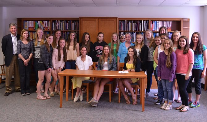 Emma Ford (seated on right) celebrated her commitment to play lacrosse for Harvard next year at a ceremony on May 10. She is joined by coach Bridget Marquardt (seated on left), her parents (far left) and the entire girls team.