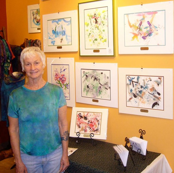 "Dorita Reyen stands beside the ""Moneigh"" exhibit currently happening at Cazenovia Artisans. Sale of the paintings to Reyen's left, painted by actual racehorses, will go to the racehorse rescue organization ReRun."
