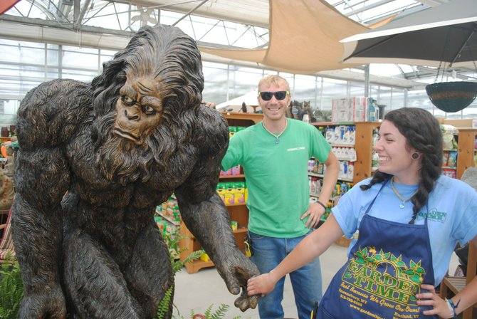 "Garden Time employees Don Probst (brother of greenhouse manager Andy Probst) and Angelica ""Daisy"" Daley welcome Bigfoot, a lifelike poly-resin outdoor statue, to the greenhouse along U.S. Route 7 in Rutland Town. The retailer is asking customers to suggest a name for the legendary apelike beast."