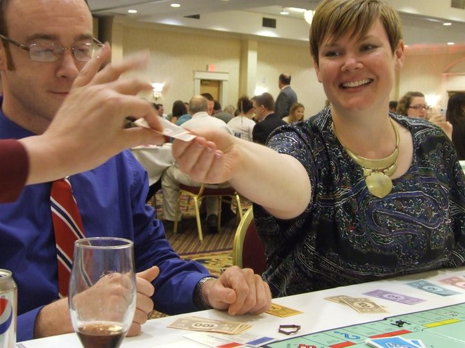 A SEFCU employee hands over cash to the banker during the 21st Annual Monopoly Tournament at The Albany Marriott on Wolf Road. This year, the event helped raise $20,000 for the Center for Disability Services, with a 21-year total of $200,000.