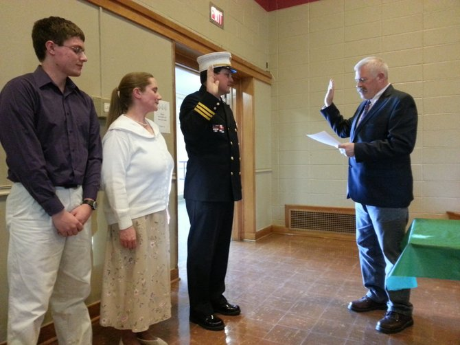 Newly- elected Manlius police chief John Buskey takes the oath while his family watches on May 14.