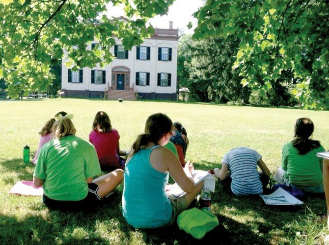 Students from last year's camp sit in the grass and sketch the front facade of Lorenzo.