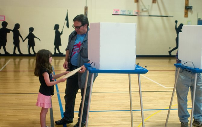 Tony Grocki hands over his ballot to his daughter, Clare, at Guilderland Elementary School on Tuesday, May 21. Voters approved Guilderland's budget by more than 60 percent, but turnout continued to decline.