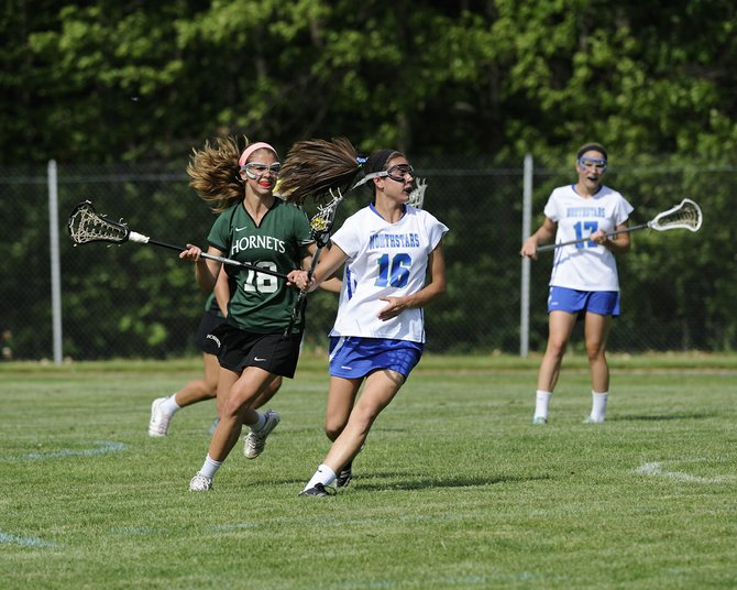 Cicero-North Syracuse freshman midfielder Meghan Duffy (16) runs away from Fayetteville-Manlius' Lindsey Trachtenberg during Wednesday's weather-delayed Class A playoff game, where the Northstars beat the Hornets 14-12 as Duffy picked up two goals and one assist.