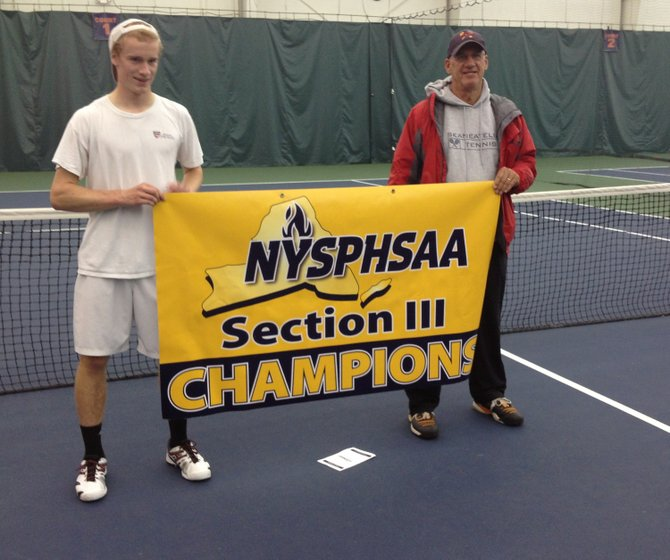 Skaneateles boys tennis player Ethan Wilcox, and head coach Joe Mushock with the Section III championship banner after Wilcox prevailed in the May 24 state qualifying tournament final over Jamesville-DeWitt's Abe Davis at Drumlins.
