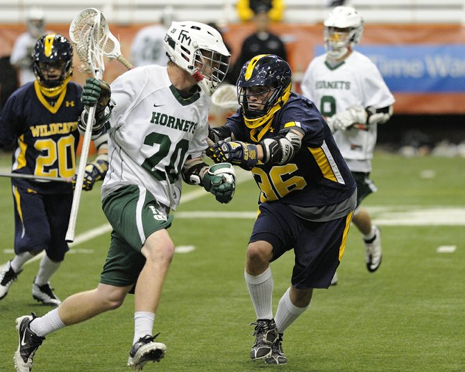 Fayetteville-Manlius midfielder Dan Cahill (20) uses one hand to maintain possession despite a check from West Genesee's David Procopio (36) during last Tuesday night's Section III Class A final at the Carrier Dome, where the Hornets lost, 7-6, in double overtime to the Wildcats.