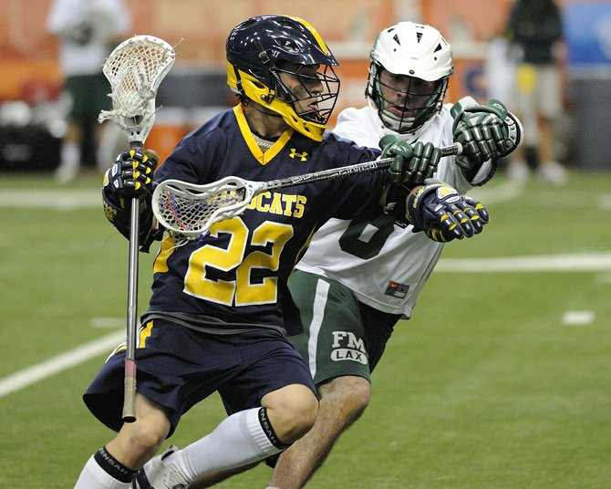 West Genesee midfielder Tom Pritchard (22) keeps possession of the ball despite a check from Fayetteville-Manlius' Kroy Arnold (8) in Tuesday night's Section III Class A final at the Carrier Dome. The Wildcats won, 6-5, in double overtime, earning an 11th sectional title in the last 12 years.