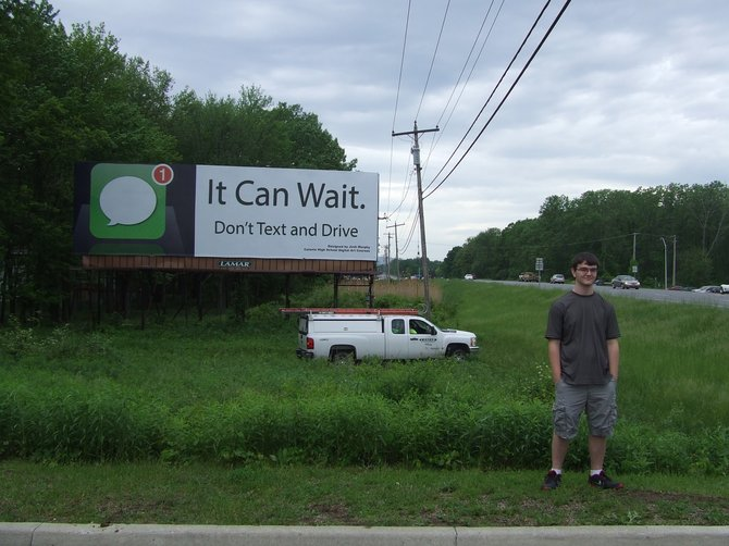 """Colonie Central High School senior Josh Murphy's slogan """"Don't Text and Drive - It Can Wait"""" and an image of the iconic iPhone text message symbol was chosen as the winning design for an anti-distracted driving billboard contest sponsored by the CCHS Art Department and Lamar Graphics."""