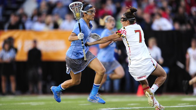 Cazenovia native Kara Cannizzaro charges up the field, defended by Maryland's Katie Schwarzmann, in last Sunday's  NCAA championship game at Villanova University. The Tar Heels would win its first national title, 13-12, in five overtimes and Cannizzaro, with four goals and two assists, would be named the tournament's Most Outstanding Player.