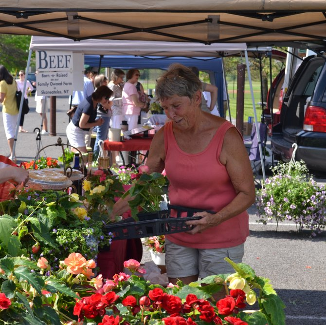 Diane Burdick of Giancarelli Farm and Farm Winery in Weedsport, puts out flowers at the Skaneateles farmers market on Thursday, May 30.