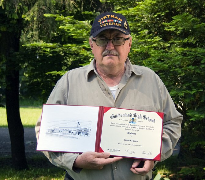 Robert Lynch stands outside his Guilderland home holding the high school diploma he was awarded by Guilderland Central School District through Operation Recognition.
