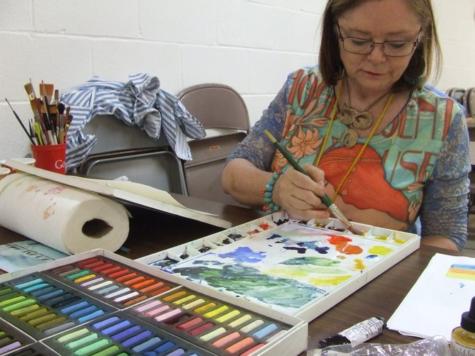 Debbie Park-Boussu mixes piant for her artwork in St. Matthew's Episcopal Church in Latham, part of the weekly gathering of the Colonie Art League.