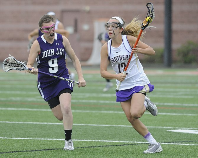 CBA freshman midfielder Maddie Cook (12) speeds past John Jay-Cross River's Mary McAvey (10) during Friday's state Class B semifinal at SUNY-Cortland. Cook picked up three goals as the Brothers defeated the Indians 17-13.