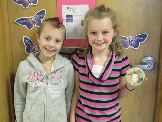 Hally Krolik, left, and friend Bronwyn Madden, stand outside their classroom at Reynolds Elementary School. Bronwyn created a button with Hally's picture on it for every team member to wear at Paige's Butterfly Run, held June 8 in Syracuse.