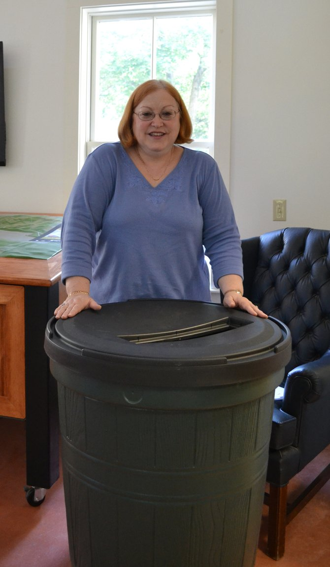 Gail Calcagnino with a rain barrel that she won at the energy challenge wrap-up event held by Sustainable Skaneateles. The barrel collects rainwater from a house's gutters to be used for watering gardens.