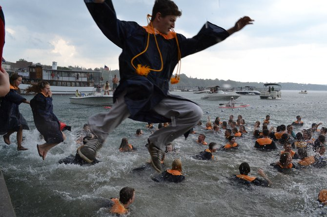 Students jump into Skaneateles Lake at the conclusion of the High School's graduation ceremony.
