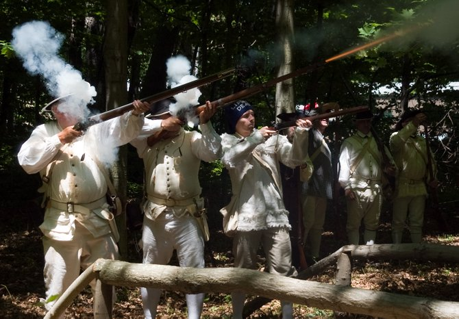 Patriots shoot at the British during a reenactment of the start of the Revolutionary War at Freedom Fest on Saturday, June 15.
