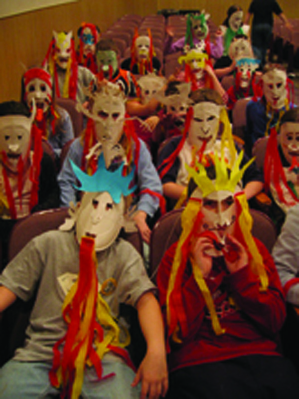 The Bromkas' students get ready to perform as dragons with their dragon masks.