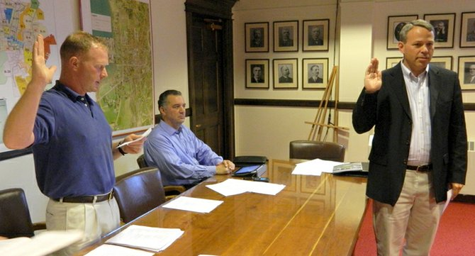 New village trustee Fritz Koennecke, right, was sworn in to office on July 1 by Mayor Kurt Wheeler, left, while Trustee Jim Joseph looks on. Wheeler and Trustee Amy Mann also resumed their seats on the board to which they were reelected during the June 18 election.
