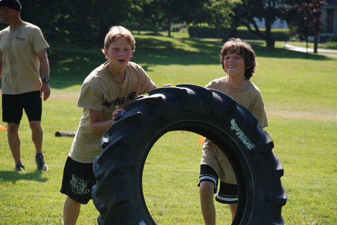 Nicholas Wamp (left) and Ethan Rhoad (right) participate in team tire flipping in Austin Park.