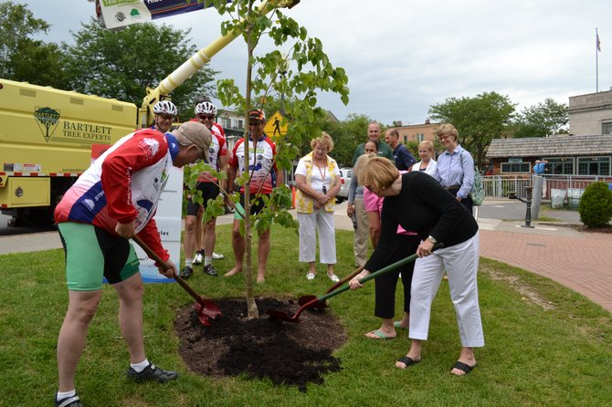 Cyclists in the Tour de Trees are joined by Skaneateles village officials and community members in dedicating a newly planted tree in Clift Park on July 29.