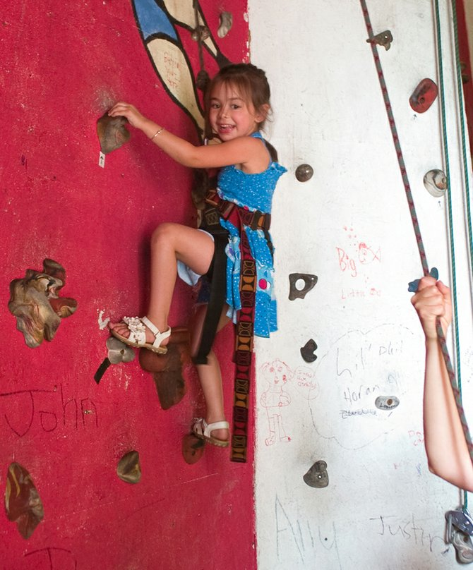 Four-year-old Alessandra, above, climbs up a rock wall at the Guilderland Rock Adventure Barn on Friday, Aug. 2. The facility recently reopened for the general public to harness up and scale its walls.