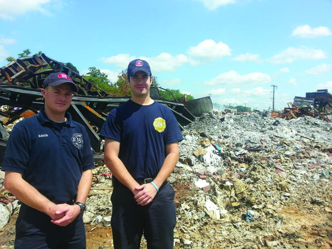 East Syracuse Fire Department Lt. Nate Baker and Lt. Ryan Russell stand in front of the rubble that once was the Syracuse Recycling and Recovery building on Carr St. One month later, the wreckage is still smoking after the July 23 fire, which burned for 72 hours straight and took the efforts of 30 fire departments to put out.