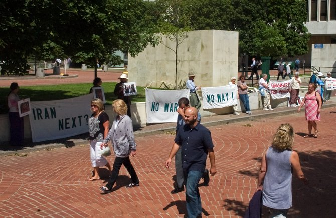 Women Against War rally at the Empire State Plaza Food Festival on Wednesday, Aug. 14, with demonstrators holding banners and photos of Iranians, along with handing out flyers. The group spoke out against entering a war with Iran and urged for peace talks.