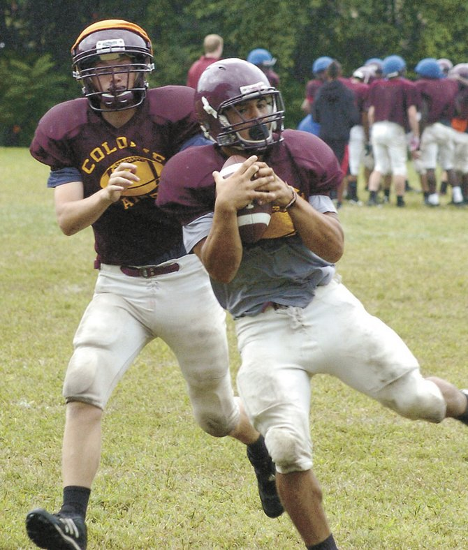 Devon Edwards, right, hauls in a pass during Monday's Colonie football practice at Roessleville Elementary School. Edwards is one of several key veterans on this year's team.