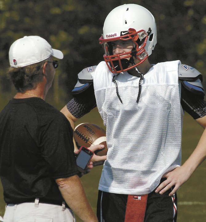 Guilderland senior quarterback Frank Gallo talks with assistant coach Garth Childs during last Wednesday's football practice. Gallo led Section II in passing last year with 1,758 yards.