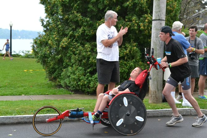Shane Lauer, who is affected by Duchenne's muscular distrophy, is pushed through the Skinnyman course on a special stroller.